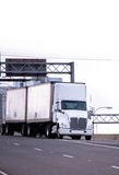 White semi truck with two trailers deliver cargo on highway Stock Image