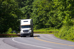 White semi truck winding green road Royalty Free Stock Photos