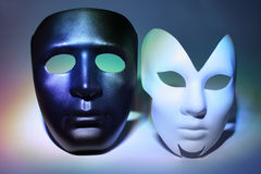 White serious and black masks (man and woman). Simple white serious and black masks (man and woman), which is colorful highlighted royalty free stock photography