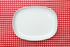 White Serving Platter Plate. On red and white checkered background Stock Photos