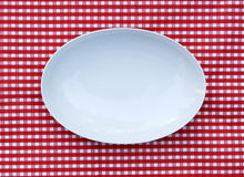 White Serving Platter Plate (oval dish). On red and white checkered background Stock Image