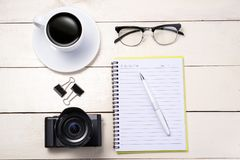 White set. Camera, pen, eyeglasses, coffee and notebook on table. Top view Stock Images
