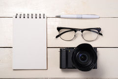 White set. Camera, pen, eyeglasses and notebook on table. Top vi. Ew Royalty Free Stock Photography