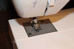 White sewing machine needle and footer closeup. Thread included in shot Stock Image