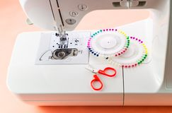 White Sewing machine and sewing supplies. Work process stock photo