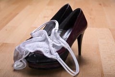 White thong pantie on black red high heels Stock Photo
