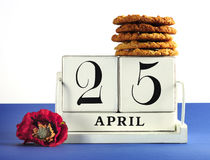 White shabby chic vintage style block calendar for Anzac Day, April 25, with traditional Anzac biscuits. On white background with remembrance red poppy Royalty Free Stock Images