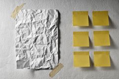 White sheet empty crumpled and yellow post it Royalty Free Stock Images