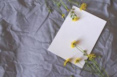 White sheet on a gray fabric background with yellow flowers stock photography