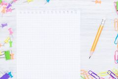 White sheet for notes and a pencil, around many different office supplies royalty free stock image