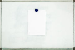 White sheet of paper attached to the old dirty magnetic board wi Stock Photography