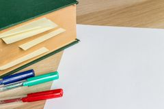 White sheet of paper and big book with marked pages. White sheet of paper and big green book with marked pages and color pencils Stock Photo