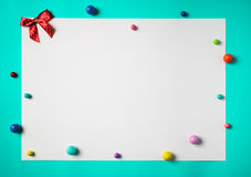 White sheet of paper with  colorful beads on cyan background Stock Images