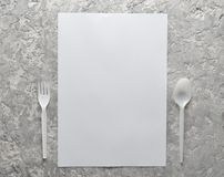 White sheet of paper for copy space, a plastic spoon and fork on a gray concrete surface. Food concept. Top view.  Royalty Free Stock Photo