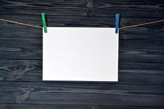 White sheet of paper fastened with a clothespin on a wooden wall. stock photos