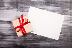 White sheet  paper and a gift red ribbon rustic wooden Stock Photo