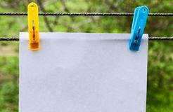 White sheet of paper hanging on clothespins stock images
