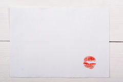 White sheet of paper with a kiss on a white table. Texture Royalty Free Stock Photos
