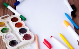 A white sheet of paper lay on a wooden table, near , pencils, paints and markers. Back to school. school and office supplies. royalty free stock photo