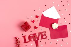 A white sheet of paper for message to loved one, red envelope, gift box, tittle sparkles,word love from black letters pen on pink. Background. Happy valentines stock image
