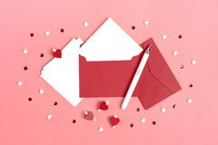 A white sheet of paper for message to loved one, red envelope, gift box, tittle sparkles,word love from black letters pen on pink. Background. Happy valentines royalty free stock image