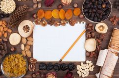 Autumn recipes. White sheet of paper with a pencil in an environment of nuts and fruits Stock Photos