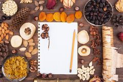 Autumn recipes. White sheet of paper with a pencil in an environment of nuts and fruits Royalty Free Stock Photo