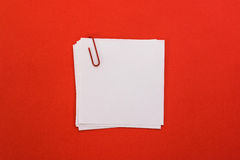 White sheet of paper with red paper clip on a red background Royalty Free Stock Photo