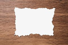 White sheet of paper scorched by fire on a brown wooden background. Layout Stock Photo