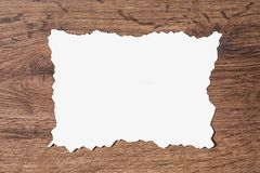 White sheet of paper scorched by fire on a brown wooden background. Layout Royalty Free Stock Photo