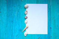 White sheet of paper (space for text), seashells, blue wood Royalty Free Stock Photo