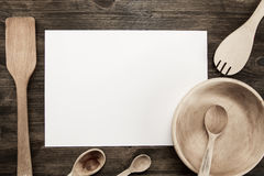 White sheet of paper with utensils on the old wooden background. Royalty Free Stock Photos