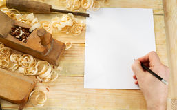 White sheet on wooden table for carpenter tools with sawdust. Copy space. Top view Royalty Free Stock Photo
