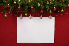 White sheet for your inscription in the new year`s layout hanging on a rope with clothespins on a red fabric background