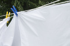 White Sheets Drying on a Clothes Line. In the summer, held on with two clothes pegs. One blue, one yellow. Blurred trees in the background stock photography