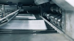 Printed sheets moving on a special conveyor, close up. stock video
