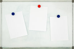 White sheets of paper attached to the old dirty magnetic board w Royalty Free Stock Images