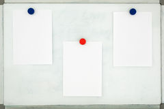 White sheets of paper attached to the old dirty magnetic board w Stock Photography