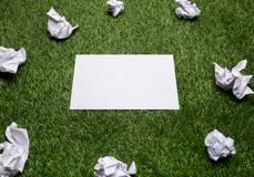 White sheets of paper with crampled sheets lying on the grass. White sheets of paper with crampled sheets lying on green grass royalty free stock image