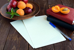 White sheets of paper for your text. Books for records and a pen in the foregroud. Ripe plums and apricots in a clay bowl in the b Royalty Free Stock Photo