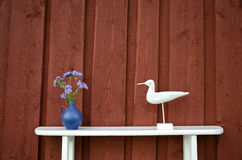White shelf near wall with flowers and wooden bird Royalty Free Stock Photo