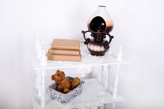 White shelves in retro style with beige book. On knitted lace napkin Royalty Free Stock Image