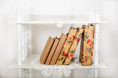 White shelves in retro style with beige book. On knitted lace napkin Royalty Free Stock Photos