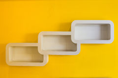 White shelves on yellow wall Royalty Free Stock Images