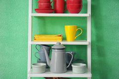 White shelving unit with ceramic dishware. Near color wall Royalty Free Stock Photography