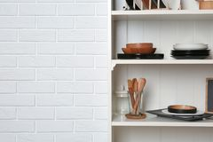 White shelving unit with set of dishware near brick wall. Space for text royalty free stock images