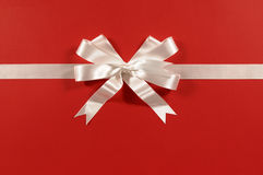 White shiny gift ribbon bow on red paper background horizontal. White gift ribbon and bow on red paper background horizontal Royalty Free Stock Images