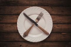 White shiny plate with folk and knife Stock Photography