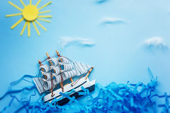 White Ship on blue wave with paper and sun. Travel and adventure concept.  Royalty Free Stock Image