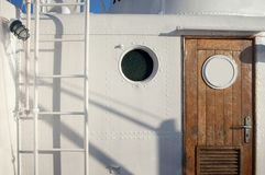 White ship cabin. Detail of white passenger ship cabin with porthole wooden doors and ladder Stock Image